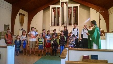 children at the altar with backpacks